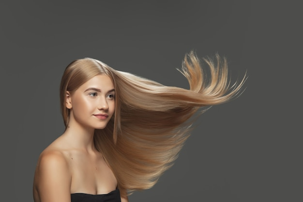 Shine. beautiful model with long smooth, flying blonde hair on dark grey studio background. young caucasian model with well-kept skin and hair blowing on air. concept of salon care, beauty, fashion.