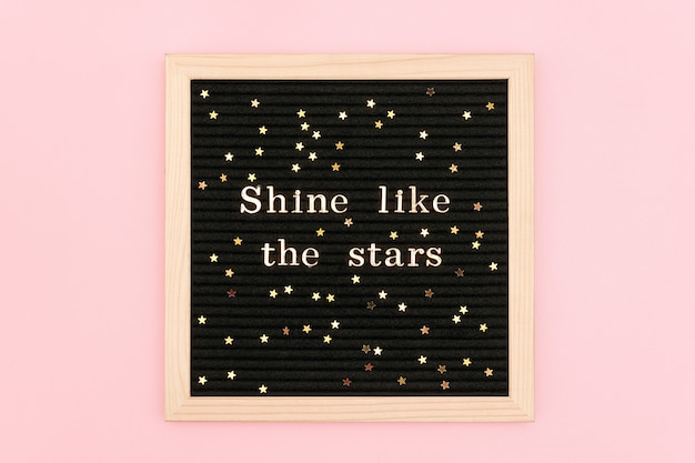 Shine like the stars. motivational quote in gold letters on black letter board and confetti stars on pink background.
