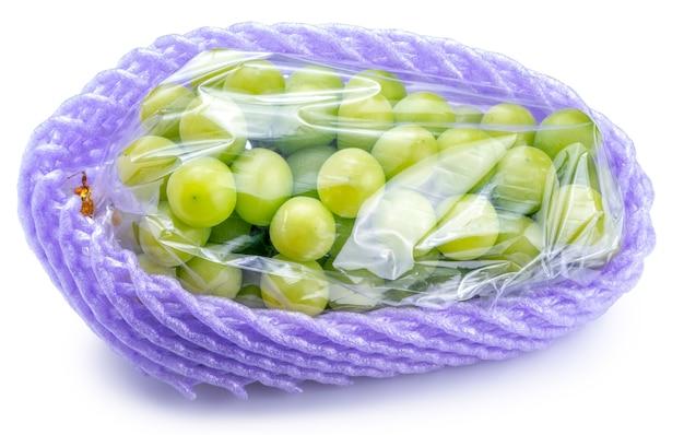 白い背景で隔離の販売の準備ができている包装でマスカットブドウを輝き、白で隔離の葉で緑のブドウ。