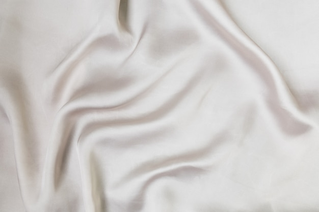 Shine silver colored satin folded and flowing background decoration design soft focus luxury fashion...