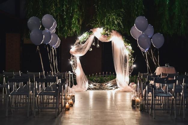 Свадебный алтарь для молодоженов стоит на заднем дворе, украшенном воздушными шарами