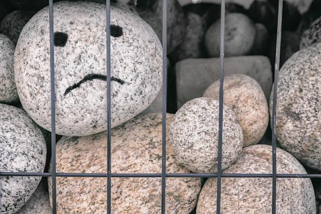 Галечный морской валун с нарисованными грустными глазами и лицом за металлической решеткой, концепция тюрьмы, отсутствие свободы, расизм, независимость людей