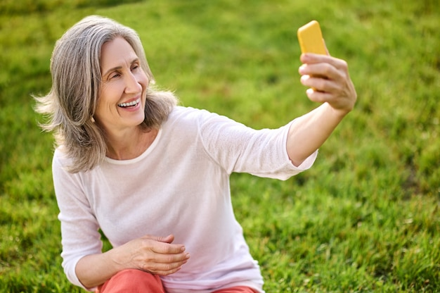 Shining adult woman with smartphone in outstretched hand