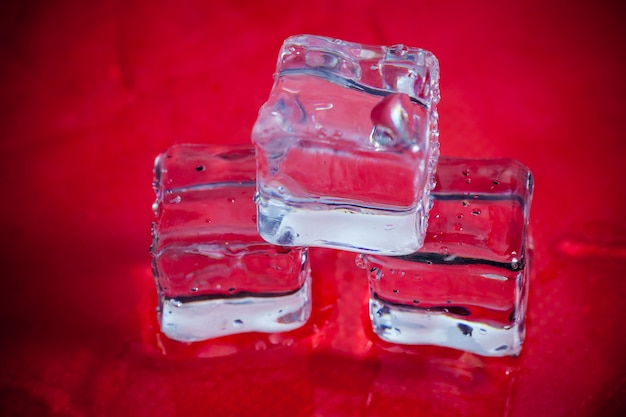 Shining ice cubes on red background.