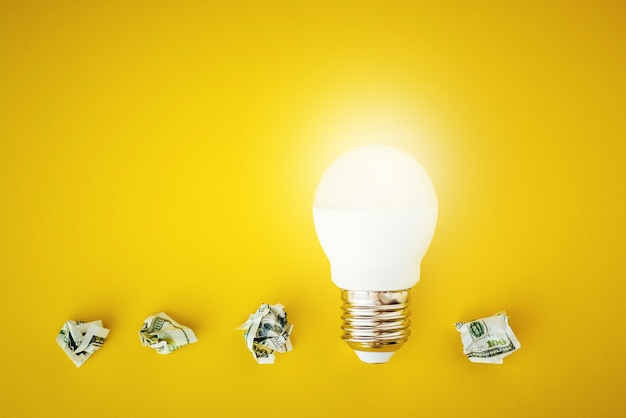 Shining lamp and crumpled paper dollar bills on yellow background