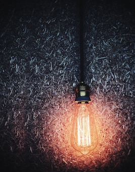 Shining light bulb hanging over dark wood pulp board background