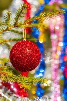 クリスマスの松の木の枝にぶら下がっている輝く赤いクリスマスボール。明けましておめでとうございますの休日の飾りのクローズアップ。前景に選択的なソフトフォーカス、背景にカラフルなぼやけた泡のボケ味。