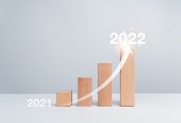 Shining rise up arrow on wooden blocks chart steps from year to year on white background with copy space, minimal style. the business growth process, and economic improvement concept.