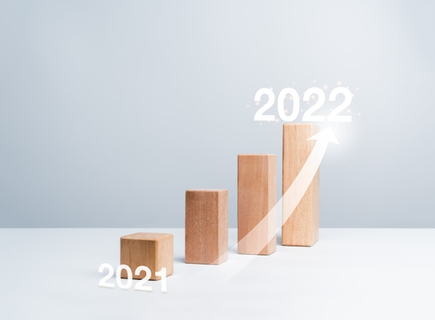 Shining rise up arrow on wooden blocks chart steps from the year to year on white background with copy space, minimal style. the business growth process, and economic improvement concept.