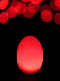 어두운 배경에 bokeh 빛으로 빛나는 스칼렛 레드 계란 모양의 테이블 램프