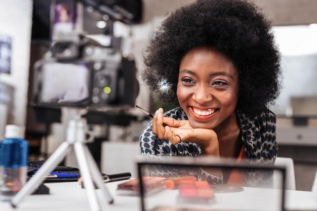 シャイニング。メイクのチュートリアルを行っている間、カメラに微笑んでいるオレンジ色のトップでアフリカ系アメリカ人の女性を笑顔