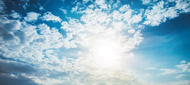 렌즈 플레어와 함께 빛나는 태양. 구름 배경으로 푸른 하늘