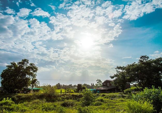렌즈 플레어와 함께 빛나는 태양. 태국의 시골 생활에 구름과 푸른 하늘
