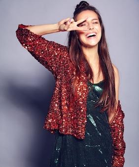 Красивая кавказская усмехаясь модель женщины брюнет битника в яркой shinny отражая куртке лета стильной и зеленом платье представляя на сером цвете. показывая знак мира