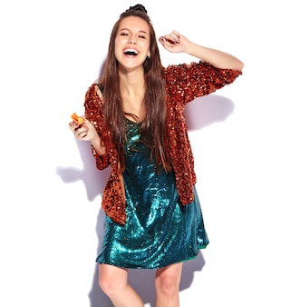 Красивая кавказская усмехаясь модель женщины брюнет битника в яркой shinny отражающей изолированной куртке лета стильной и зеленом платье. еда французского макаруна