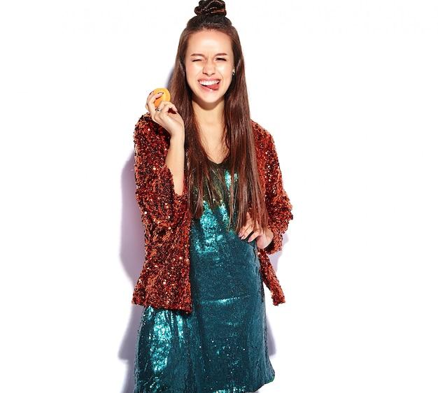 Красивая кавказская усмехаясь модель женщины брюнет битника в яркой shinny отражающей изолированной куртке лета стильной и зеленом платье. едят французское миндальное печенье и показывают ее язык