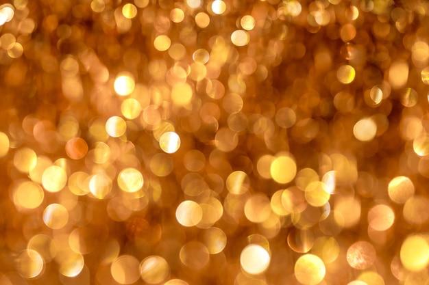 黄金のボケ味を持つ光沢のある抽象的なお祭りの背景