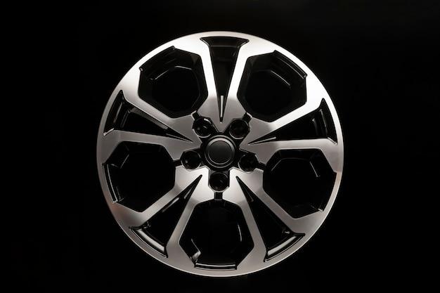 Блестящие литые диски нового дизайна в форме звезды, вид спереди, на черном фоне.