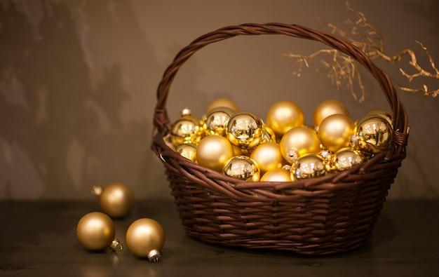光沢のあるマットなクリスマスツリーは、木の枝が付いた籐のバスケットに金色のおもちゃを入れます