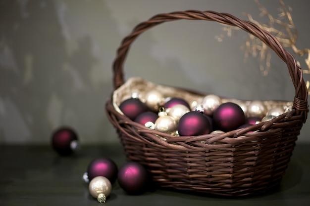 枝のある籐のかごの中の光沢のあるマットなクリスマスツリーのおもちゃの銀色とほのかな色