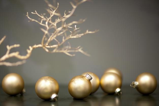 光沢のあるマットな金色のクリスマスツリーのおもちゃと灰色の背景の木の枝