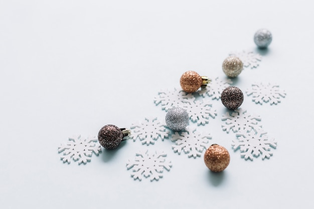 Shiny baubles with small snowflakes on table