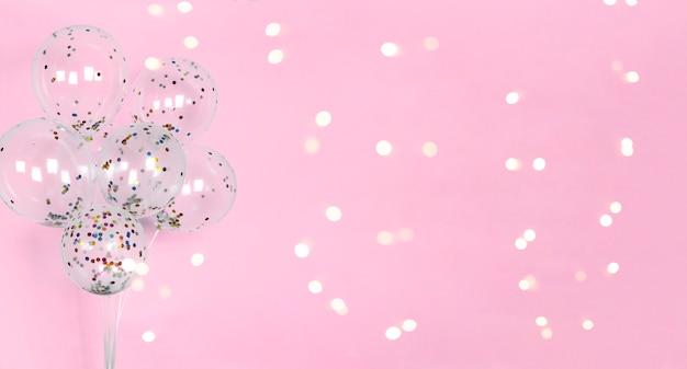 風船でお祝いのピンクの背景に光沢のあるボケライト