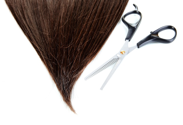Shiny brown hair with scissors isolated on white