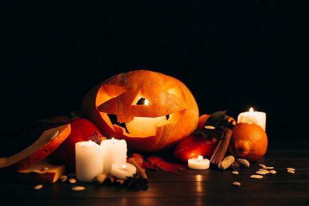 무서운 할로윈 호박 앞에 빛나는 촛불, 계피 및 낙엽이 서 있습니다.
