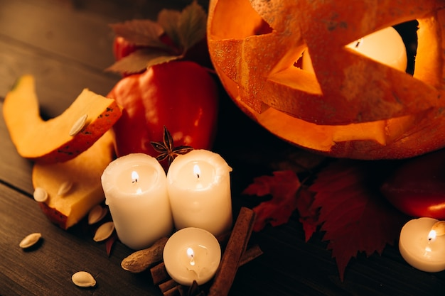Shiny candles, cinnamon and fallen leaves stand before scarry halloween pumpkin