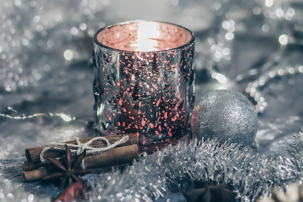 Shiny candlestick with a burning candle on a silver background with festive decorations. flat lay card