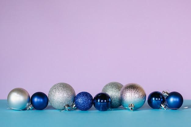 青、白、銀色の光沢のあるクリスマスボールは、ターコイズとピンクの背景に一列に配置されます