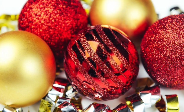 Shiny christmas balls red and golden with confetti of foil.