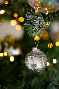 Shiny christmas decoration ball of sequins, against background of branches and lights