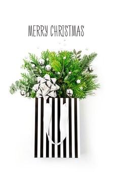 光沢のあるクリスマスの装飾と白い背景の上のショッピングバッグのモミの枝。クリスマスの買い物のコンセプト。フラットレイ、上面図