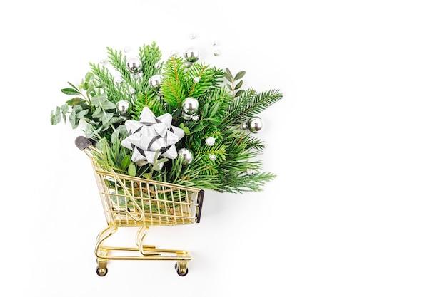 白い背景の上のショッピングカートの光沢のあるクリスマスの装飾とモミの枝。クリスマスの買い物のコンセプト。フラットレイ、上面図