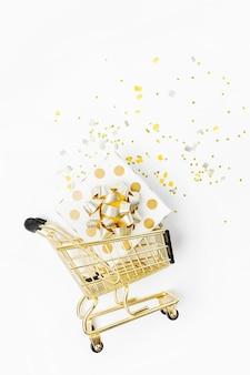 光沢のあるクリスマスの装飾と白い背景の上のショッピングカートの金の弓との贈り物。クリスマスの買い物のコンセプト。フラットレイ、上面図
