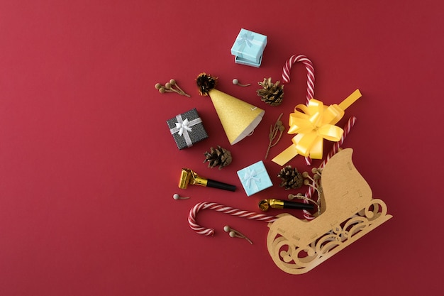 Shiny christmas decorations and santa's sleigh on red background. shopping and gifts concept. christmas shopping concept. flat lay, top view