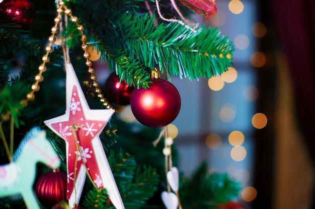 Блестящий рождественский красный шар висит на сосновых ветках с праздничным фоном
