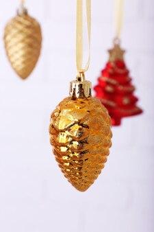 Shiny christmas toys hanging on light blurred background