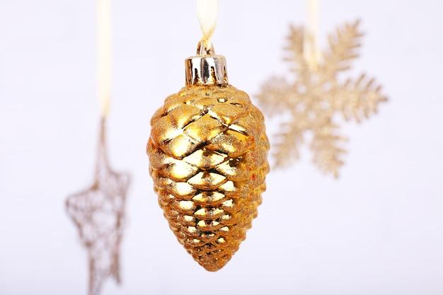 光のぼやけた表面にぶら下がっている光沢のあるクリスマスのおもちゃ
