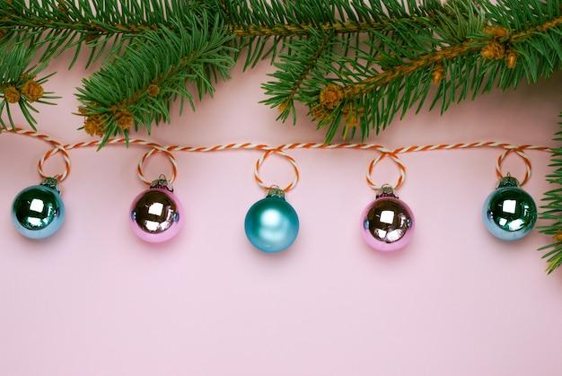 Блестящая рождественская гирлянда с розовыми и голубыми шарами на розовом