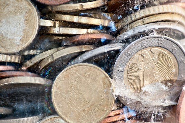 Shiny euro coins frozen in ice with german coin in front