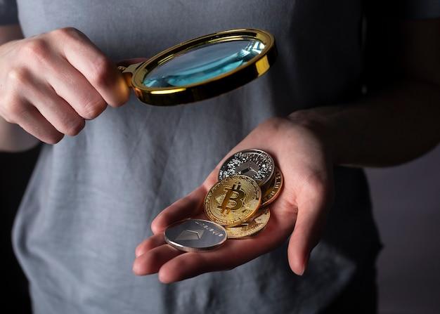 拡大鏡のある女性の手のひらにある暗号通貨の光沢のある金と銀のコインをクローズアップ。ビットコインと他の暗号通貨の山。
