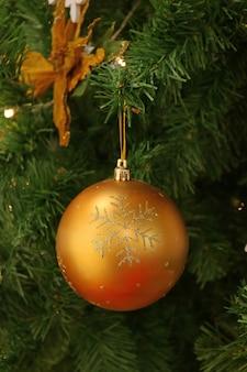 Shiny gold ball shaped christmas ornament hanging on the christmas tree