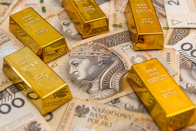 Shiny gold bar on polish zloty. investment and financial concept. currency