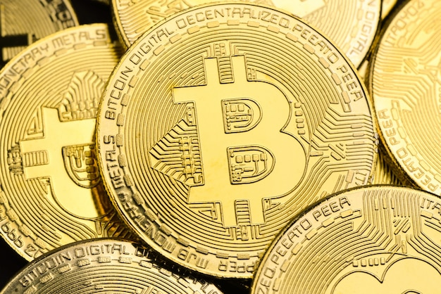 Shiny gold bitcoins as background,  cryptocurrency and virtual money concept