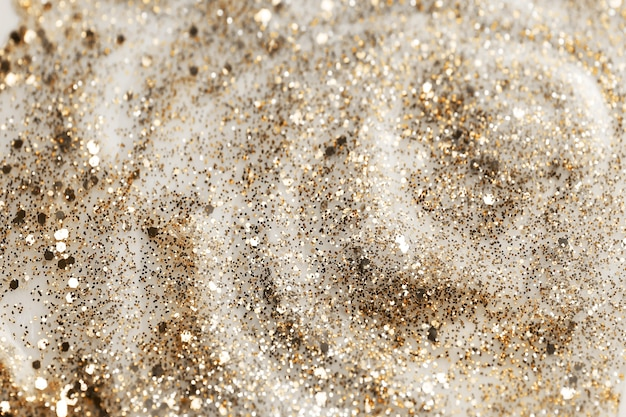 Shiny gold glittering background with soft selective focus. nail polish texture.