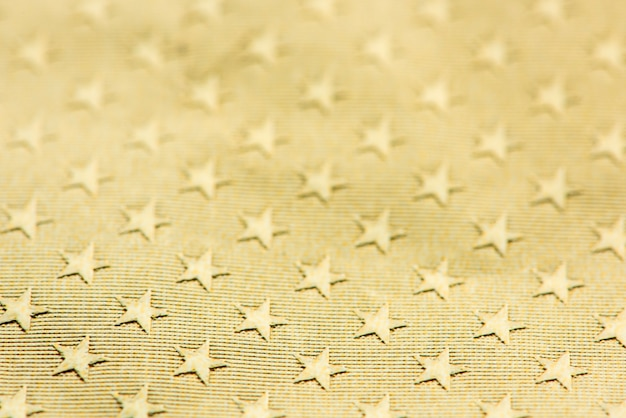 Fondo di carta con motivo a stella strutturato oro lucido