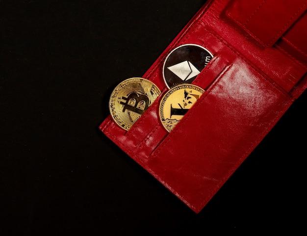 光沢のある金色のビットコインとイーサリアムの銀貨、黒の背景に赤い財布のポケットにライトコイン。新しい通貨の概念、上面図。
